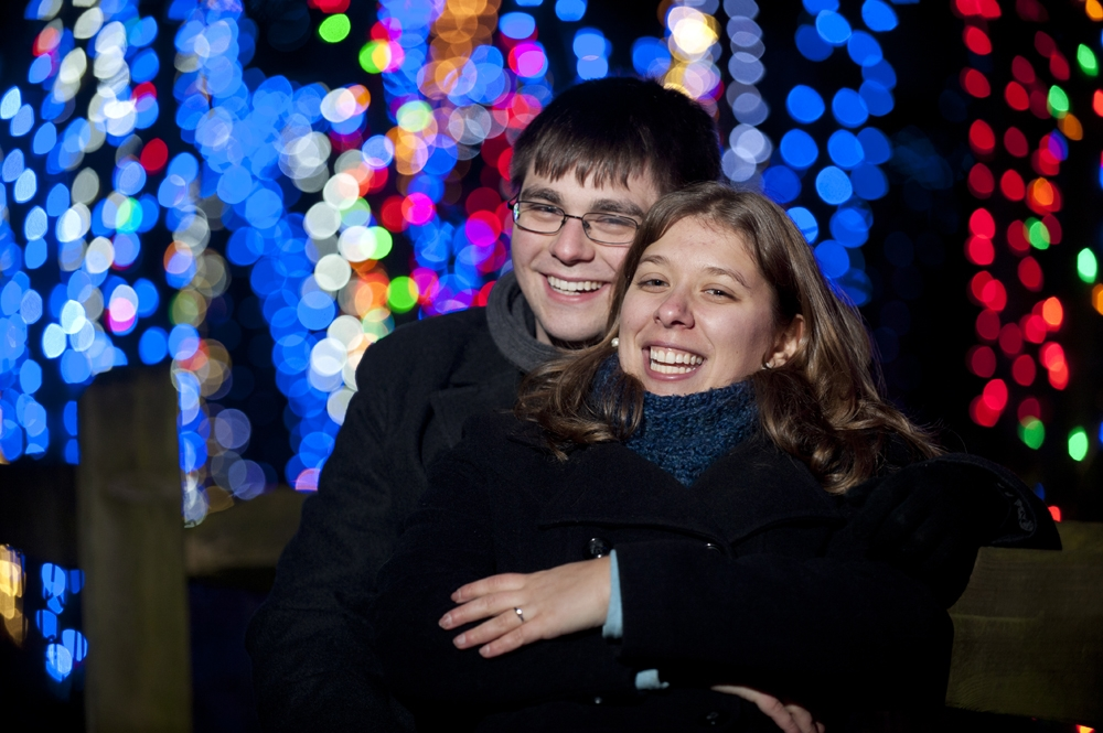Engagement Photography - Hugging in front of Christmas Lights