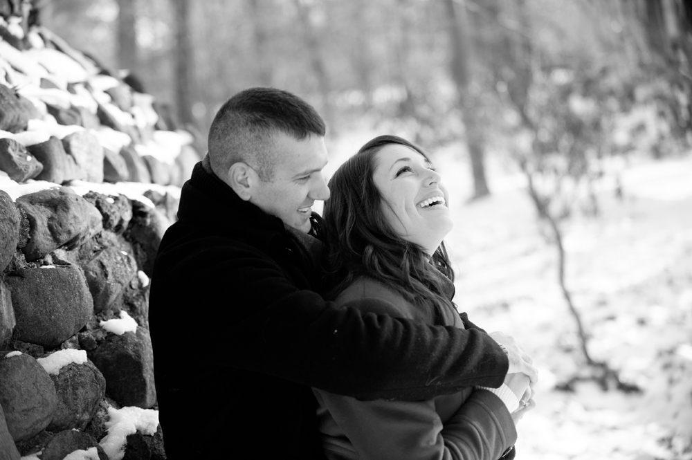 Engagement Photography - Winter couple hugging and laughing against stone wall