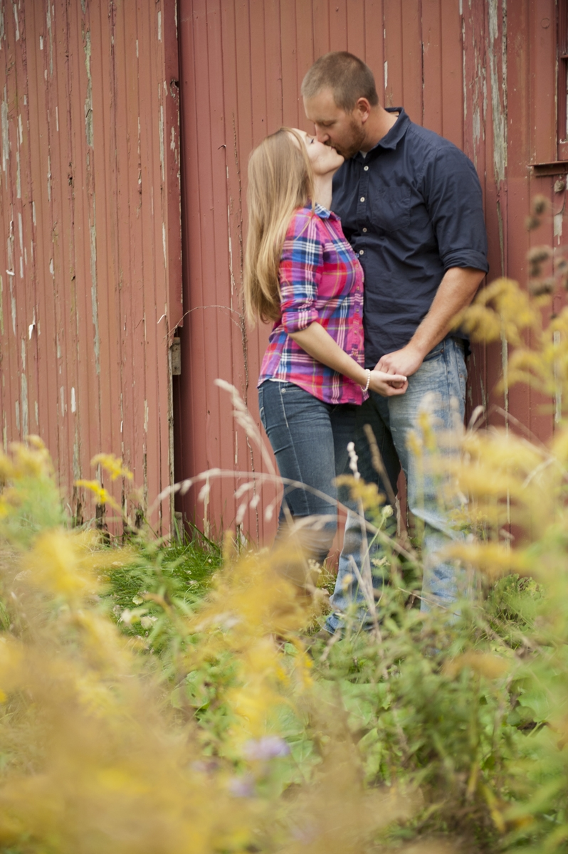 Engagement Photography - Rustic couple holding hands and kissing against country barn
