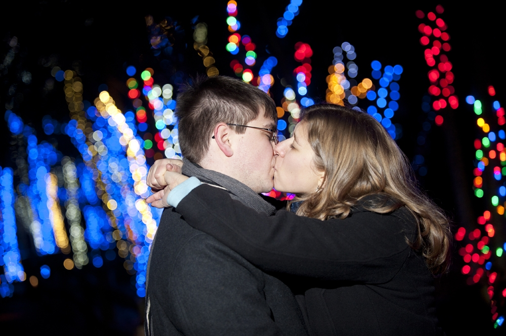 Engagement Photography - Kissing in front of Christmas Lights