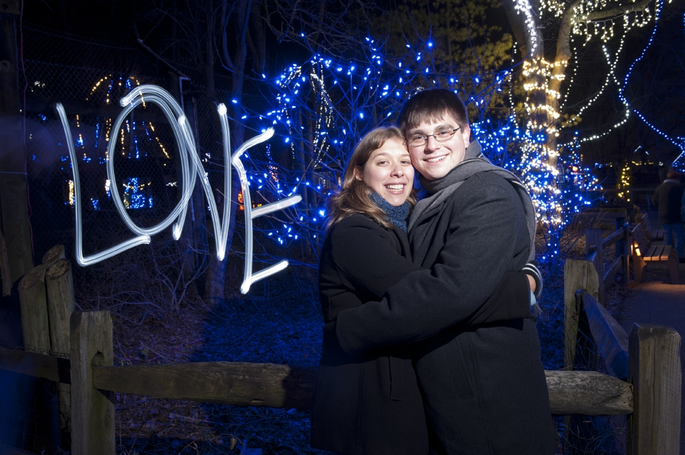 Engagement Photography - long exposure hugging in front of Christmas lights