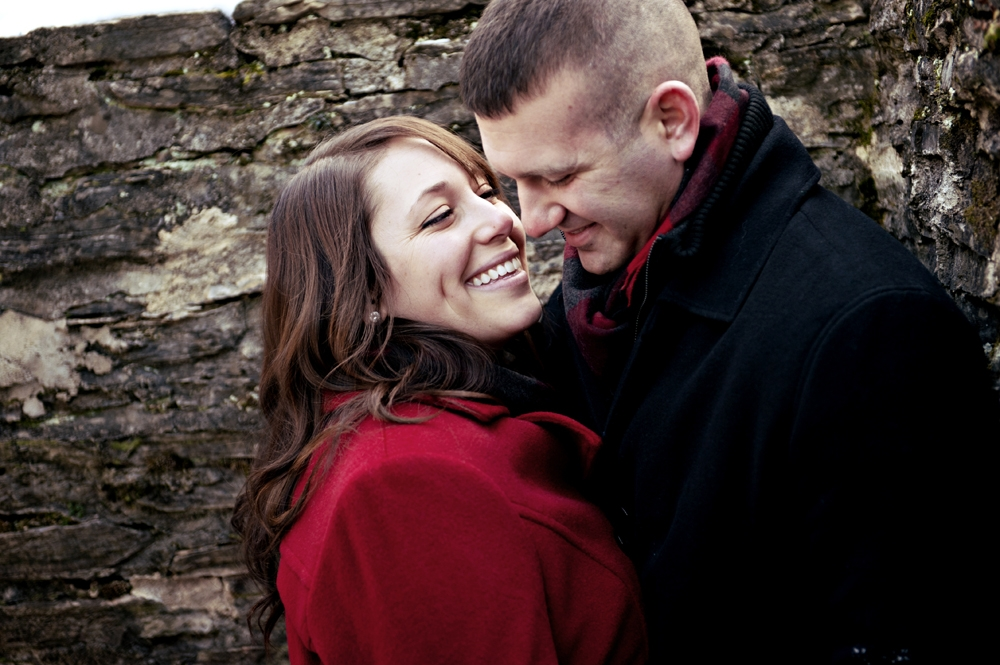 Engagement Photography - Winter couple embracing next to stone wall