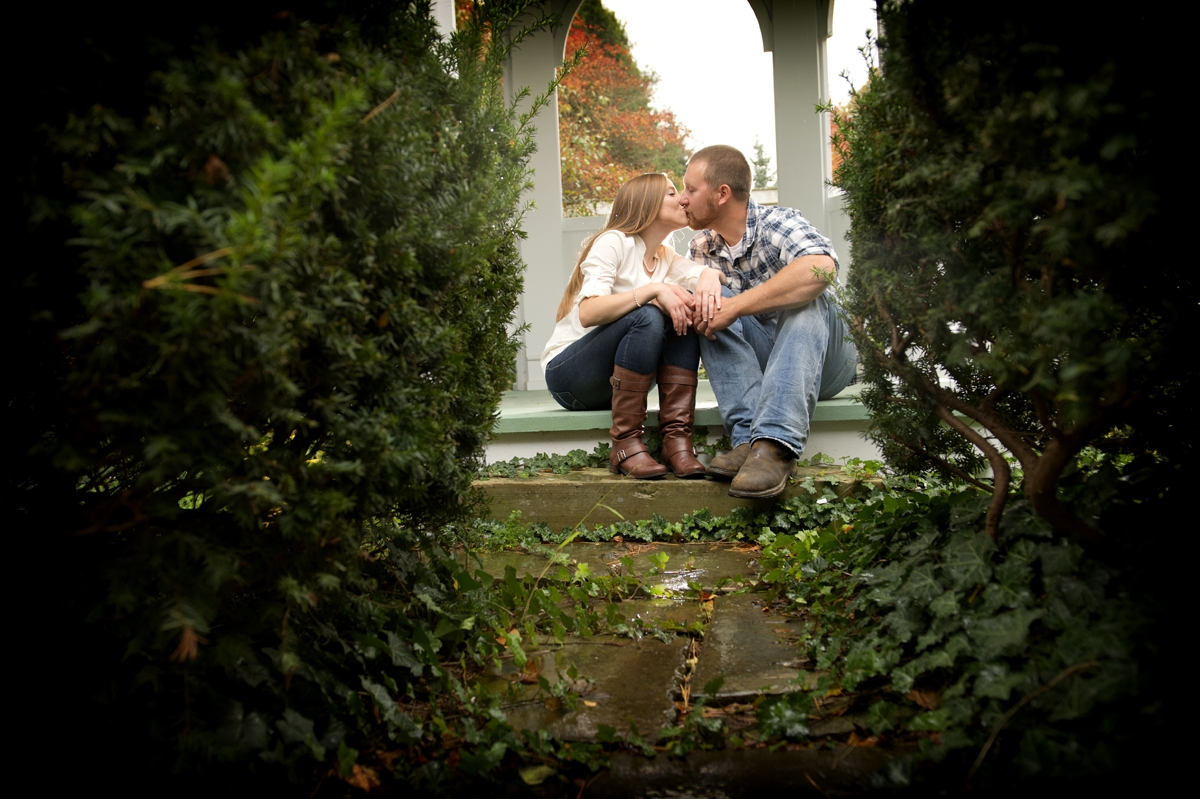 Engagement Photography - Couple kissing between vines and bushes in Autumn