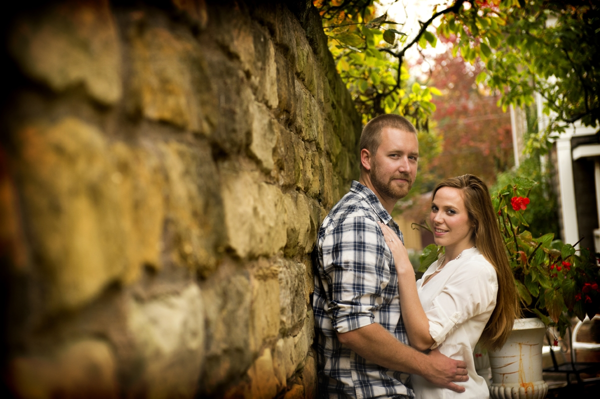 Engagement Photography - Couple hugging against stone wall in autumn