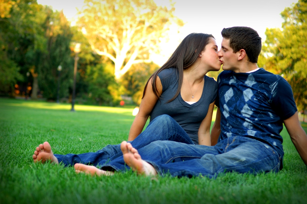 Engagement Photography - Outdoor couple kissing while relaxing in the grass